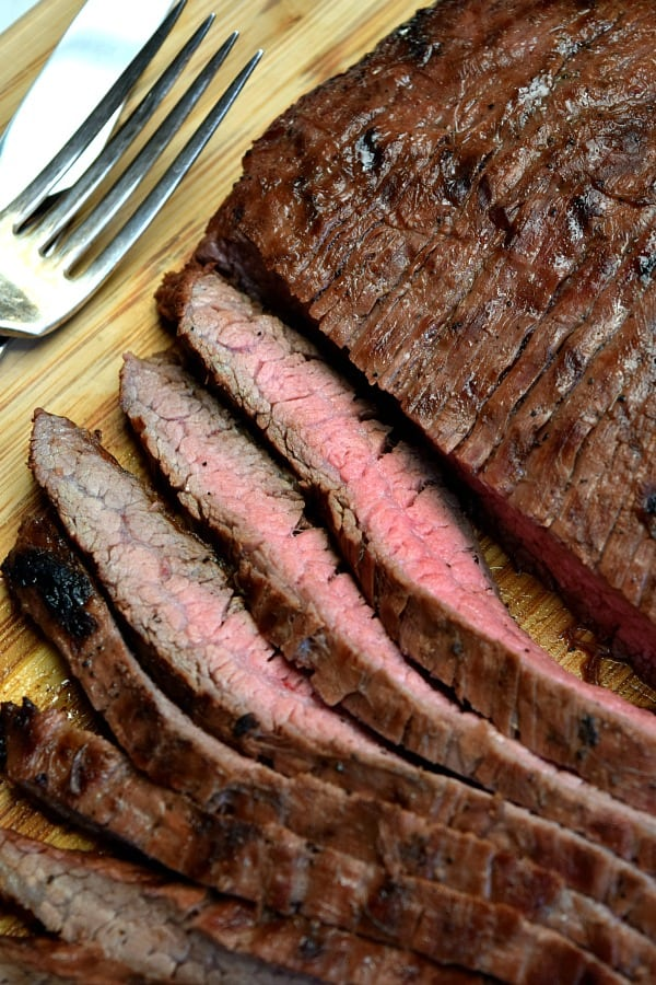 Grilled Flank Steak on a cutting board half cut into strips