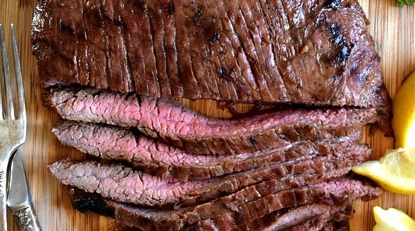 Overhead shot of grilled flank steak, half cut into strips showing off the pink meat inside