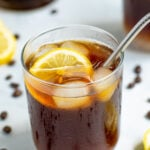Pinterest Pin for Coffee Lemonade with a glass of coffee with ice, lemon slices, and a metal straw