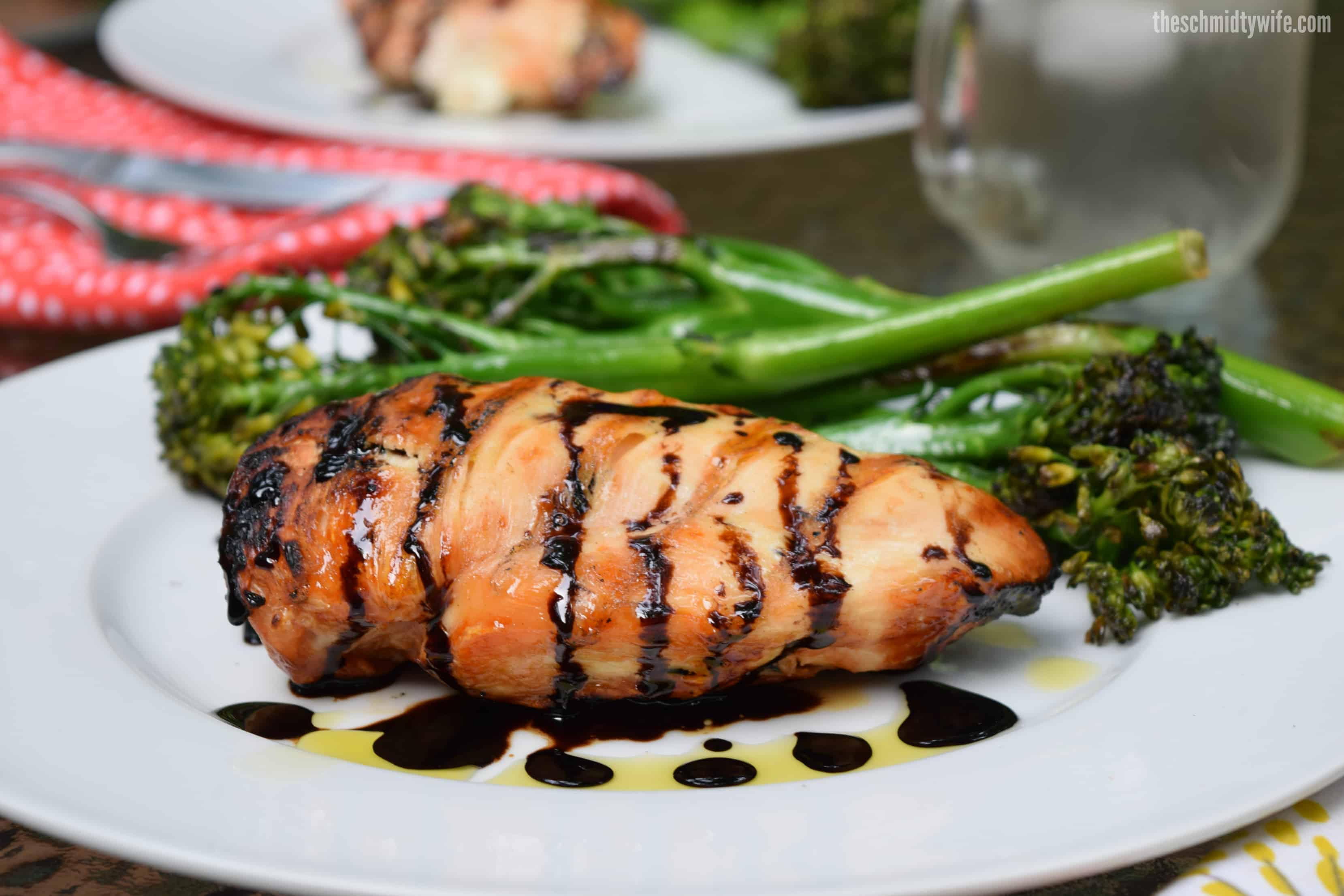 Stuffed Caprese Chicken grilled to perfection and sitting on a plate with broccolini