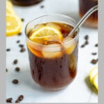 Pinterest Pin for coffee lemonade showing a photo of a glass of coffee with ice and a lemon wedge with a metal straw