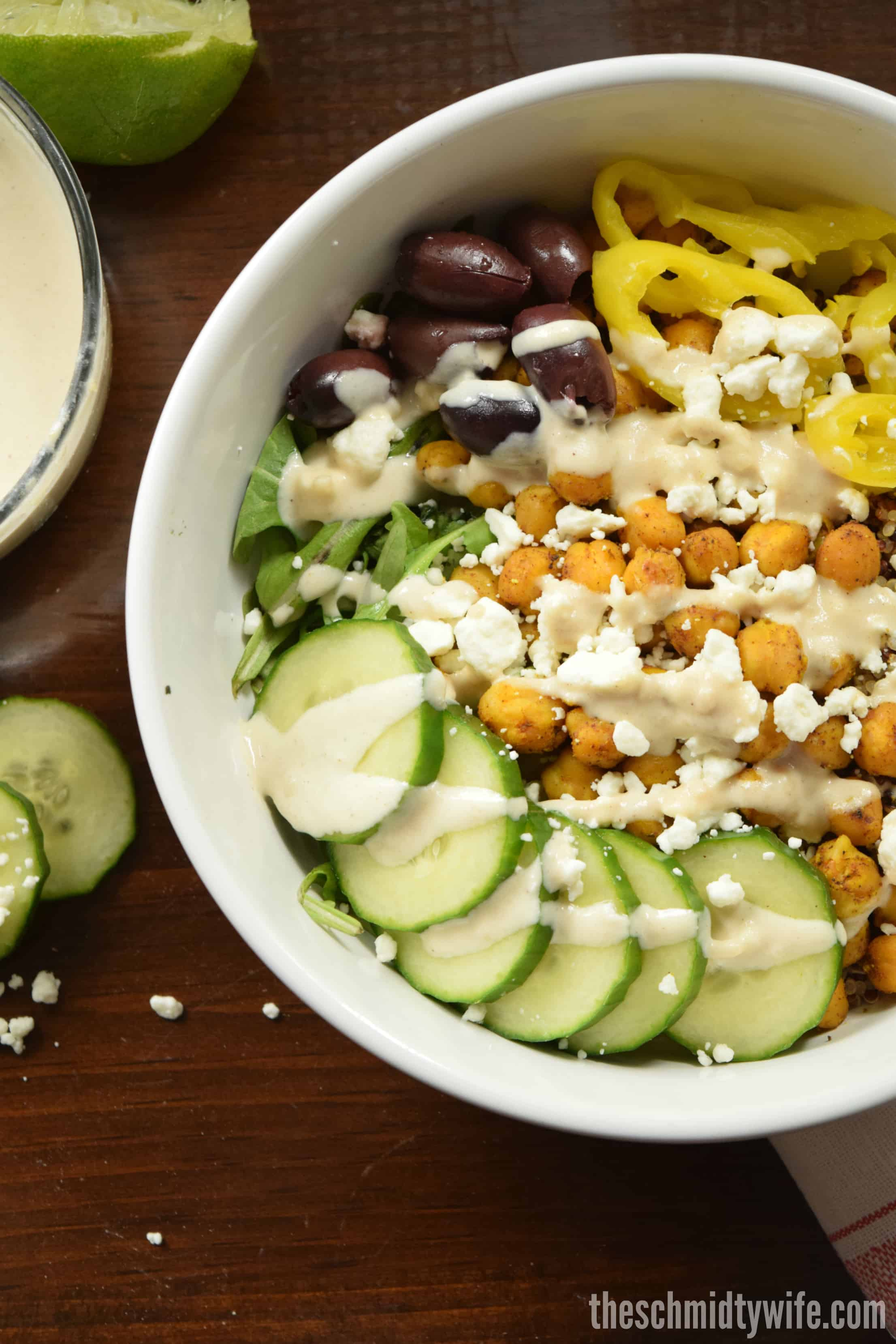 Chickpea Shawarma Buddha Bowl on a wood table with sauces and veggies