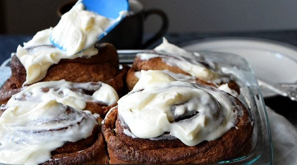 Overnight Gingerbread Cinnamon Rolls being frosted with cream cheese frosting