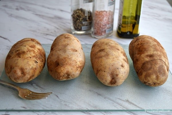 4 potatoes sitting on a cutting board