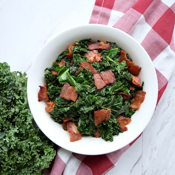 overhead shot of Sauteed Kale with Bacon in a white bowl