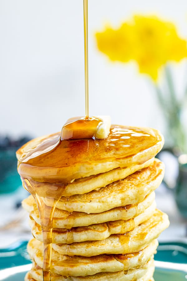 close up of maple syrup being poured onto a stack of pancakes