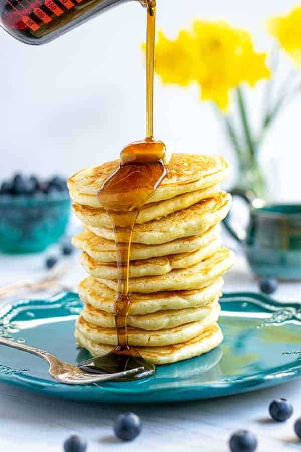 syrup being poured onto a tall stack of pancakes made from scratch