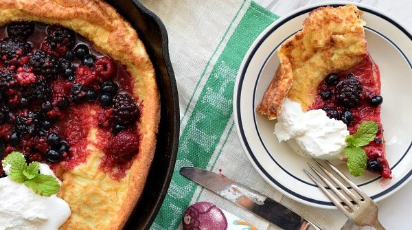a slice of Dutch Baby with Berries and Whipped Cream