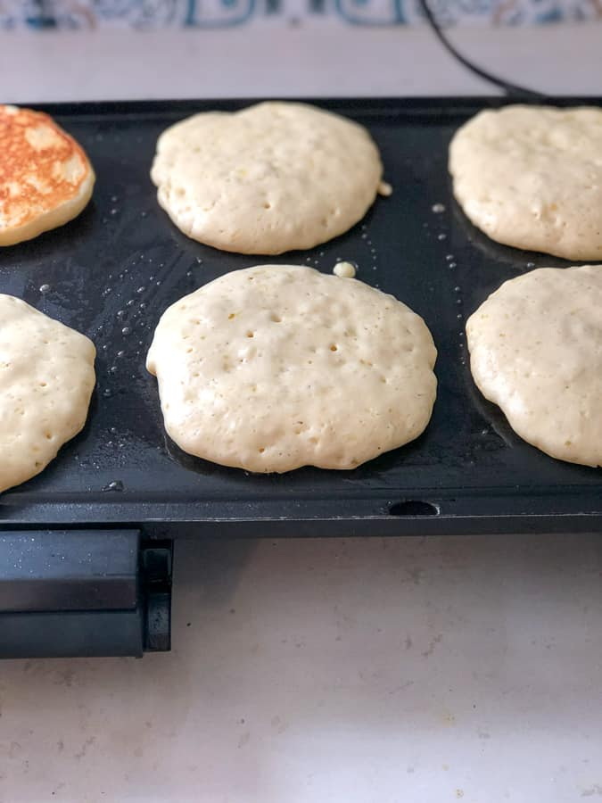 pancakes cooking on a griddle with air bubbles beginning to pop in the middle so you know when to flip the pancake