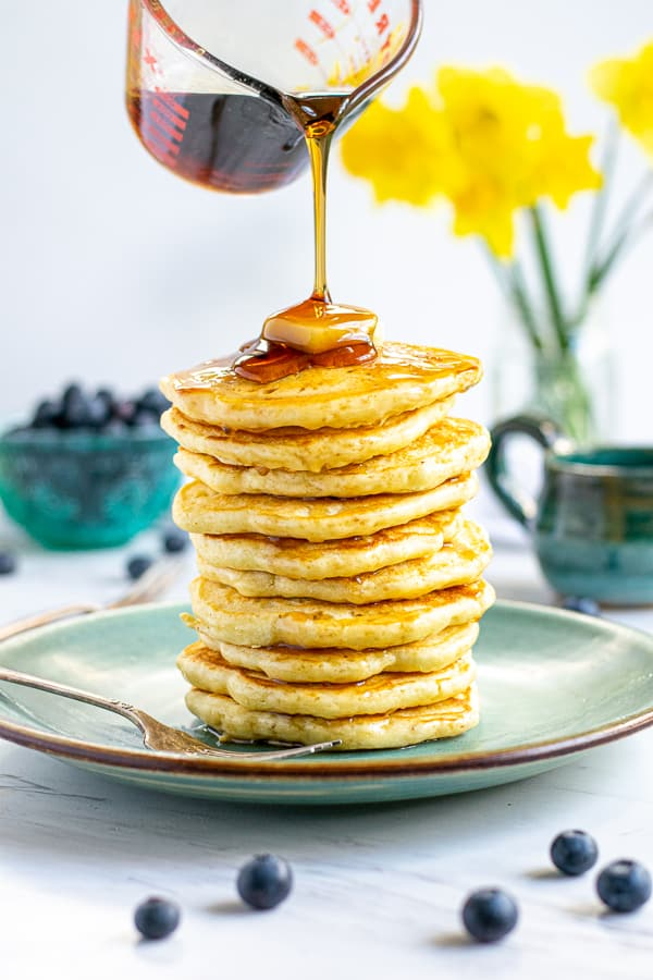 syrup being poured on a tall stack of fluffy pancakes
