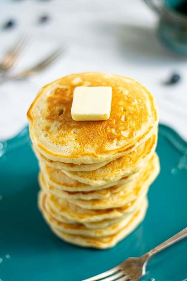Top of a stack of pancakes with a pad of butter on top