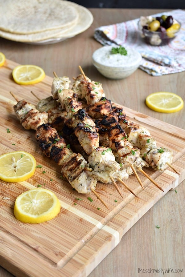 Marinated and Grilled Greek Chicken Kabobs sitting on a wooden cutting board next to some tzatiki sauce