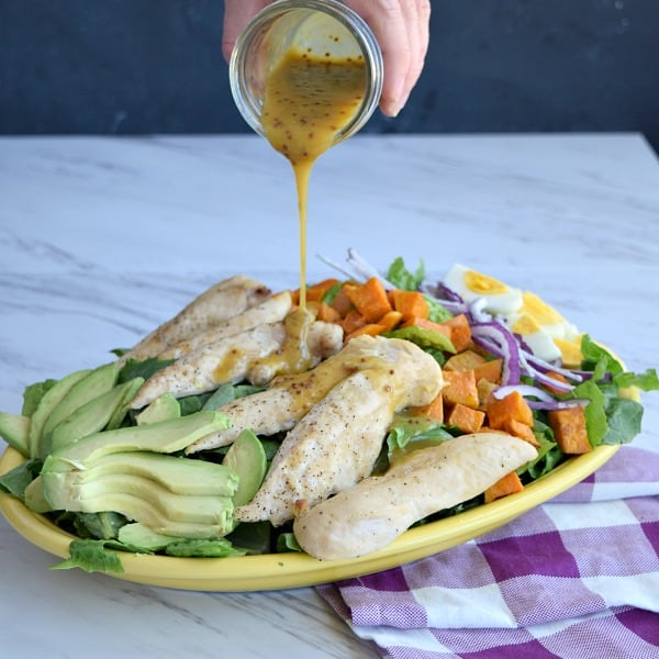 Honey Mustard Dressing being poured onto the salad