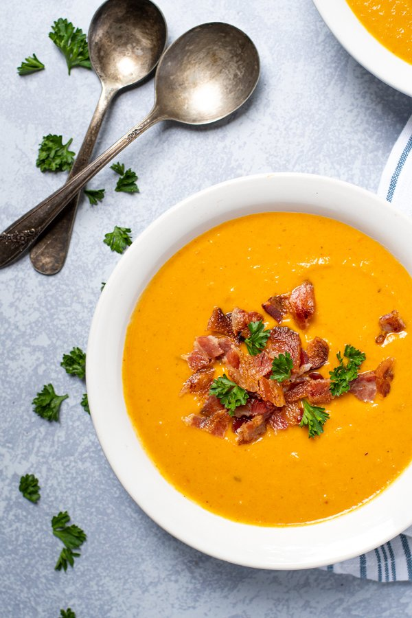 Overhead view of a white bowl full of roasted butternut squash and carrot soup garnished with bacon crumbles and fresh parsley.