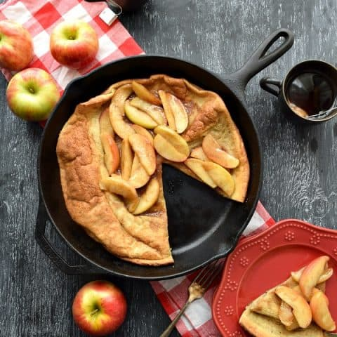 Overhead Cinnamon Apple Topped Dutch Baby with a slice cut out