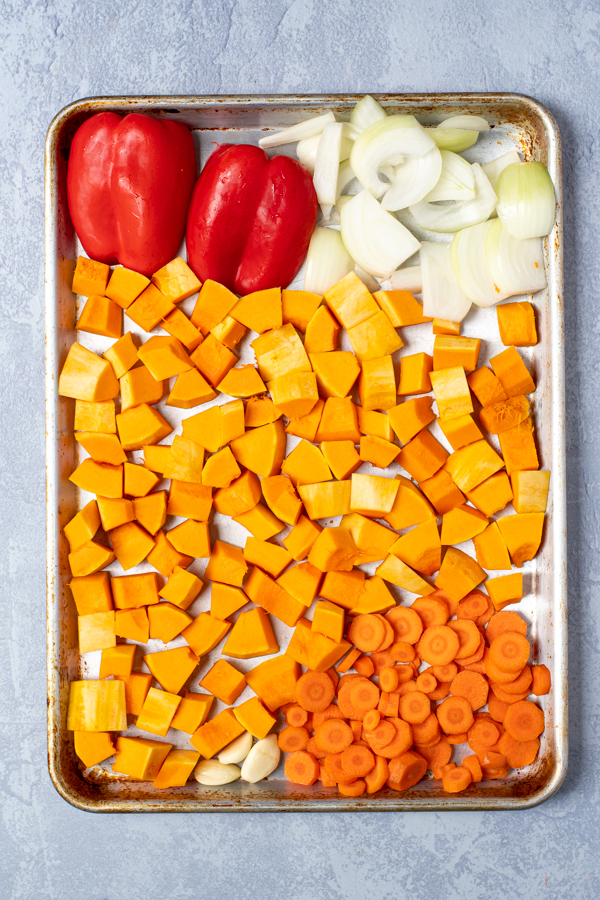 Overhead view of a sheet pan with freshly diced butternut squash, carrots, and onion with halved red bell peppers.