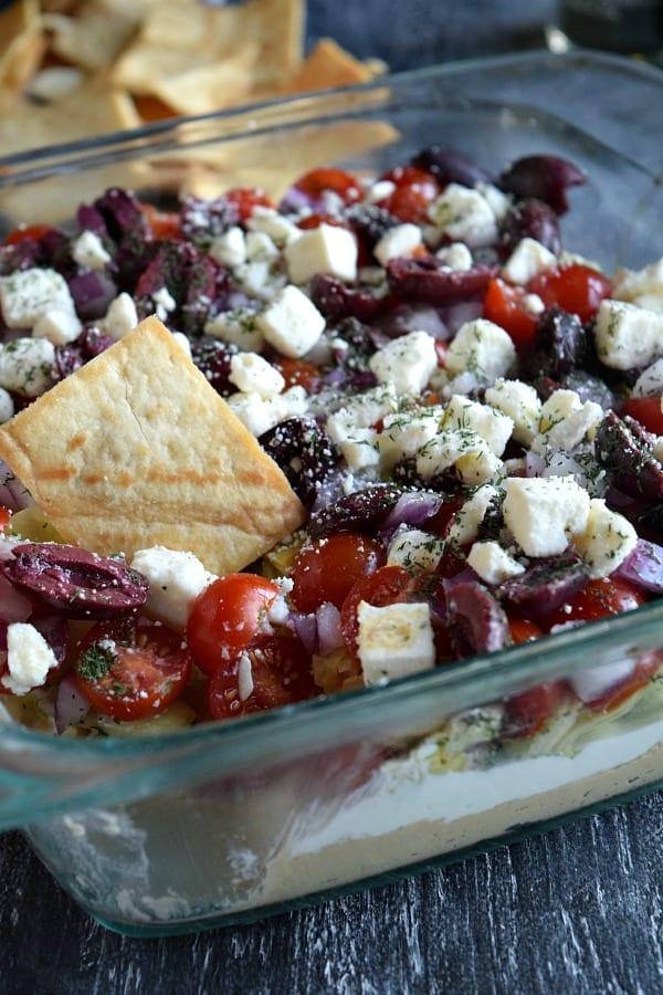 Pita Chip dipped into Greek Layer Dip