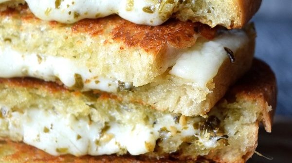 Pesto Grilled Cheese stacked up with melting cheese and pesto