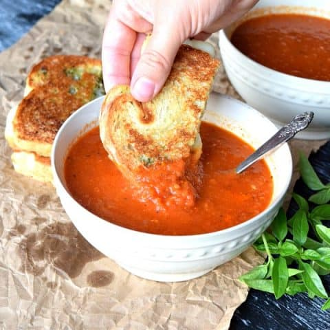 Roasted Red Pepper & Tomato Soup with a grilled cheese being dipped in