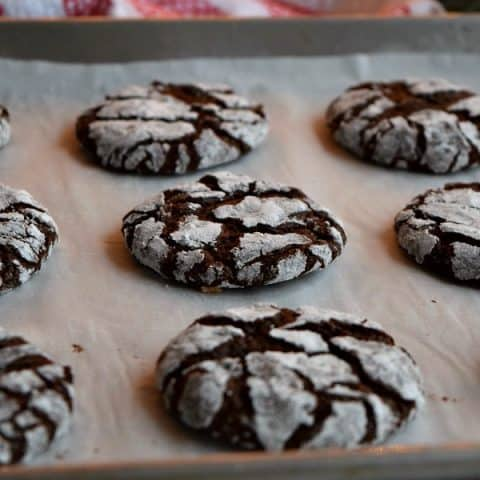 close up of a chocolate peppermint crinkle cookie on a baking sheet
