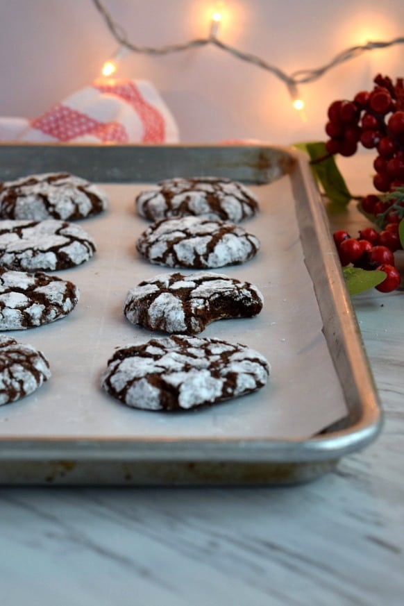 baking tray with chocolate peppermint crinkle cookies, one has a bite taken out