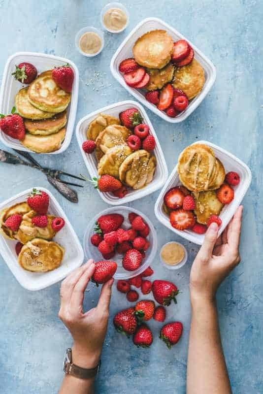 healthy to go meal prep pancakes in 5 plastic containers with berries