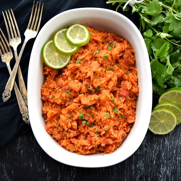 overhead shot of mexican rice with limes, cilantro, and forks