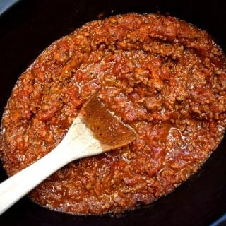 close up view of bolognese sauce in the crockpot with a spoon