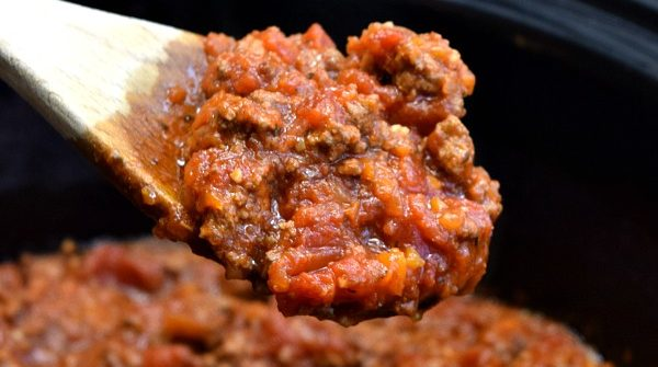 a large spoon full of bolognese sauce over top a crockpot