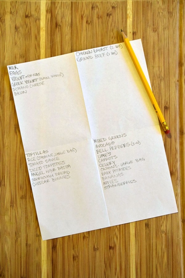 a grocery list divided into 4 sections with a pencil