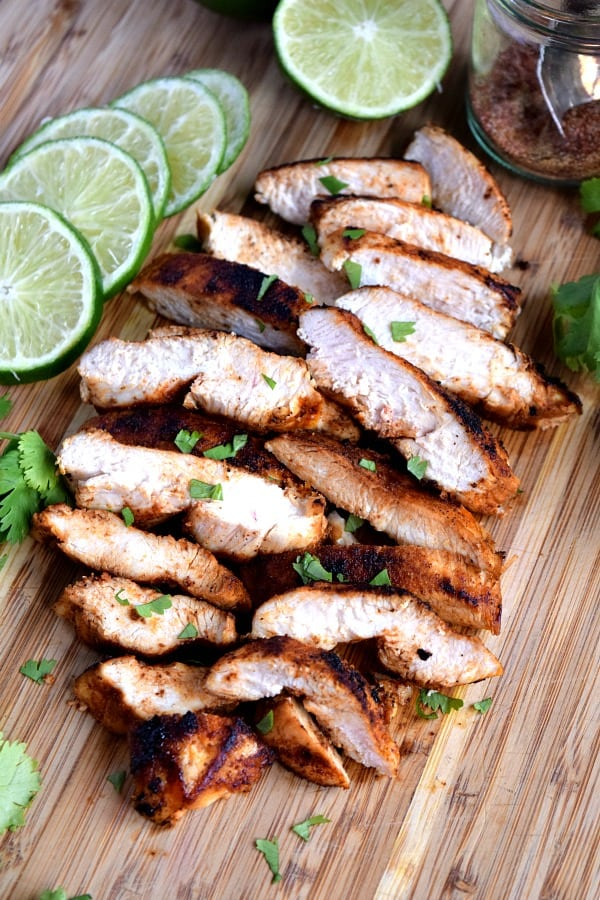 Southwest Chicken sliced and piled up on a cutting board with limes and cilantro