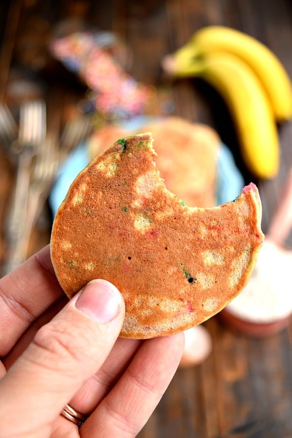 a close up of a mini whole wheat banana pancake with sprinkles and a bite taken