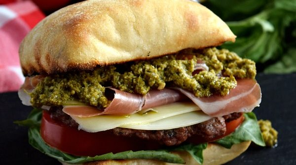 a close up of a prosciutto pesto burger on a black plate with a beer