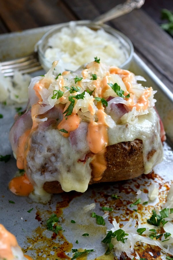 Reuben Stuffed Baked Potato covered with sauerkraut and dripping with 1,000 island dressing