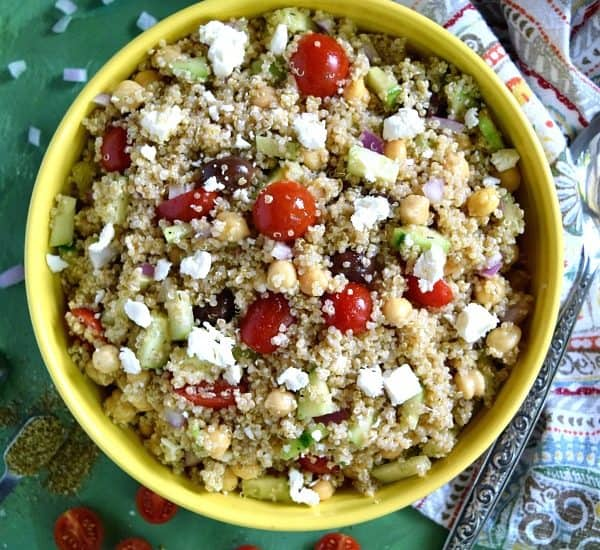 Greek Quinoa Chickpea Salad in a big yellow bowl with a napkin on a green background