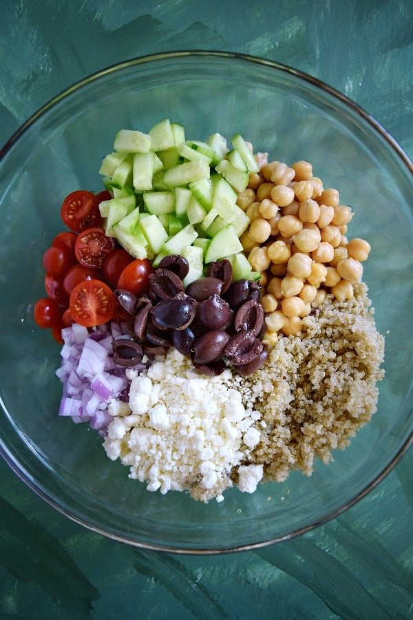 all of the ingredients for Greek Quinoa Chickpea Salad in a bowl waiting to be tossed with dressing
