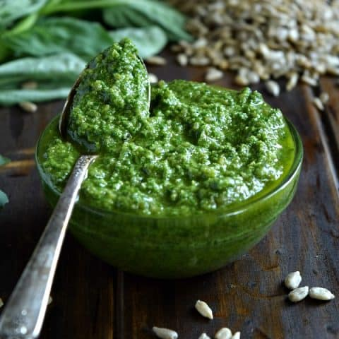 Sunflower Seed Basil Pesto in a small bowl with a spoonful ready to be spread and tossed with your next meal