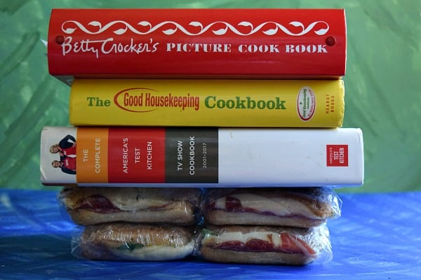 Italian Pressed Picnic Sandwich being pressed down by large cookbooks
