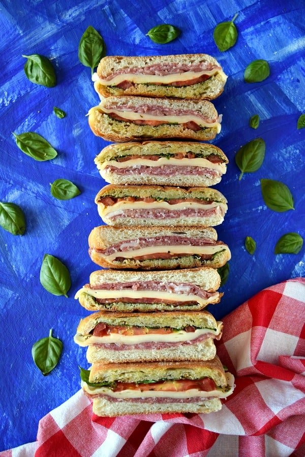 Italian Pressed Picnic Sandwich with a picnic napkin and basil leaves on a blue background
