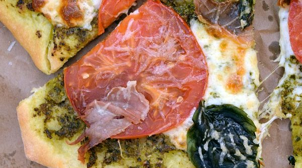 a slice of Pesto Pizza with Prosciutto, Tomatoes, and Mozzarella