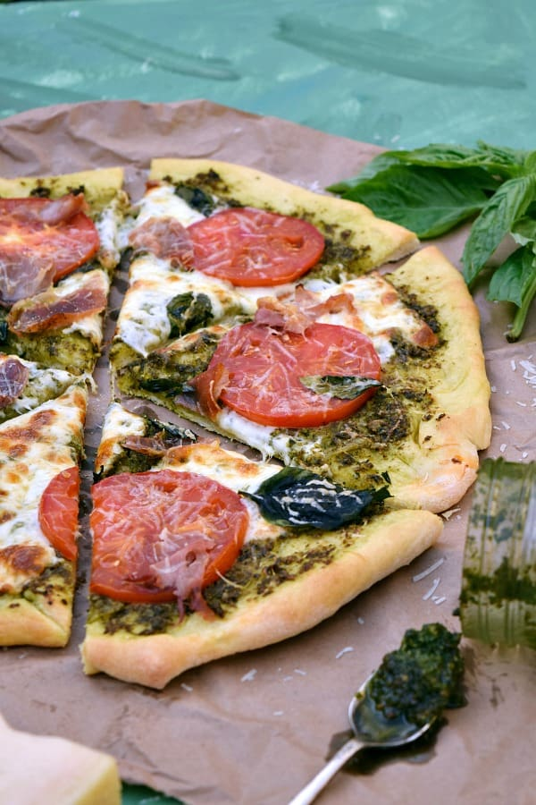 a close up shot of a few slices of Pesto Pizza with Prosciutto, Tomatoes, and Mozzarella
