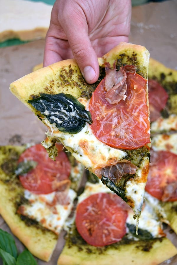 Pesto Pizza with Prosciutto, Tomatoes, and Mozzarella slice being held by a hand ready to be eaten