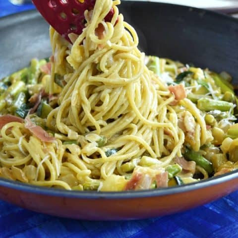 Summer Spaghetti Carbonara being pulled out of a large skillet showing the pasta covered in creamy carbonara sauce