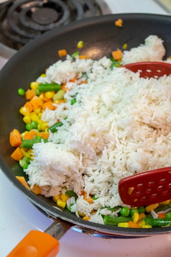 vegetables and rice being tossed in the skillet