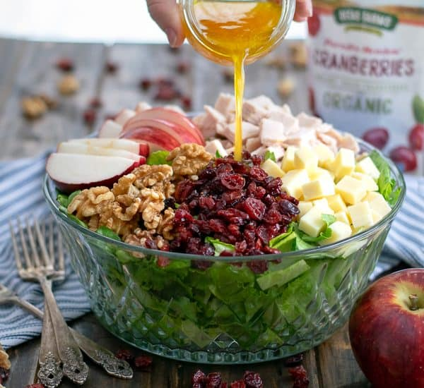 Apple Cider Vinaigrette being poured onto an Apple Cranberry Salad with turkey, walnuts, and cheddar cheese