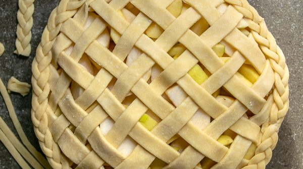 all butter pie crust used to make a lattice top and braided decorated edge on an apple pie