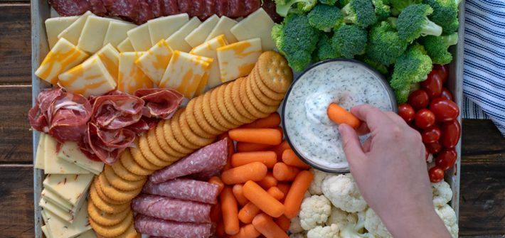 dipping into a dip on a snack platter
