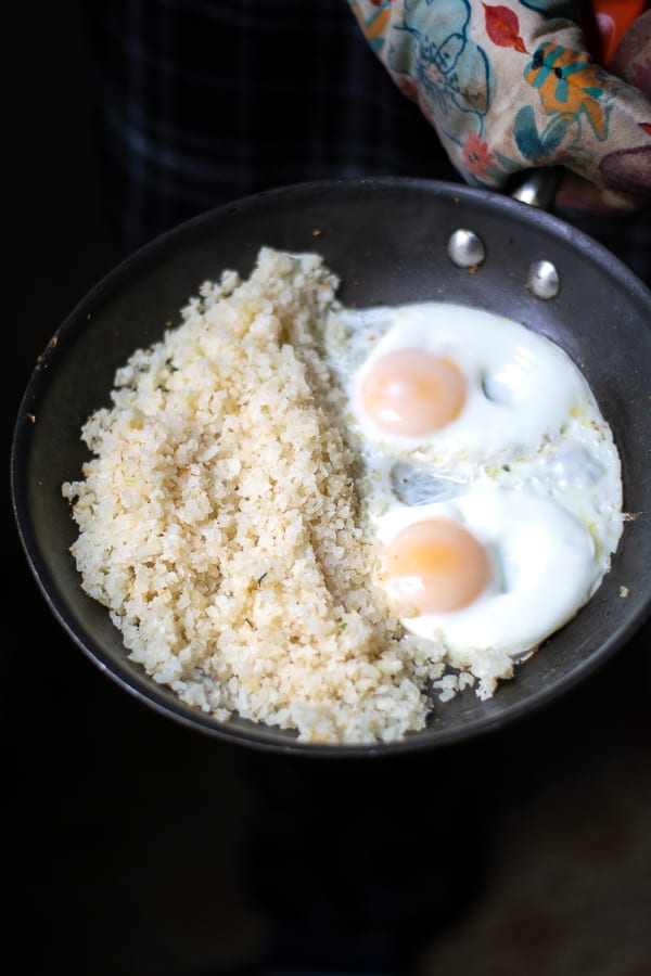 cauliflower rice and fried eggs in a skillet
