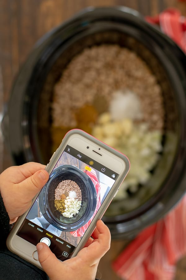 a picture of a toddler taking a picture of the ingredients for crockpot refried beans