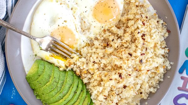 overhead shot of a plate full of breakfast eggs with cauliflower rice and avocado